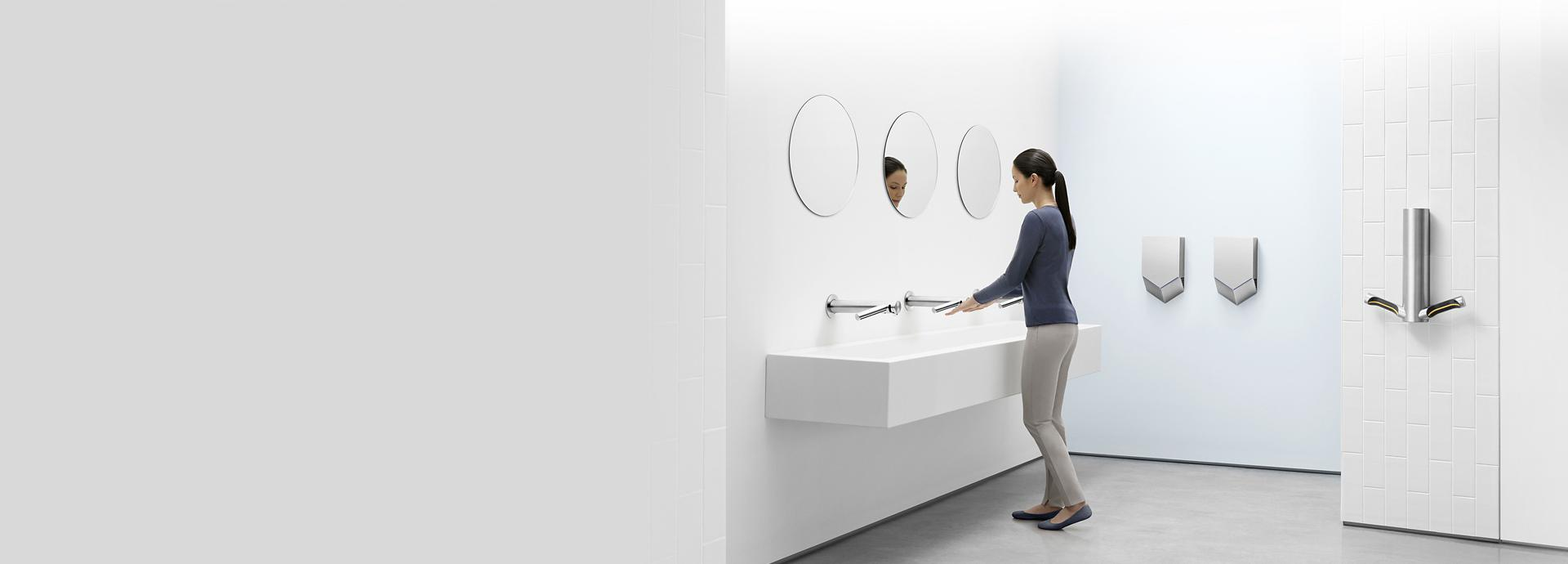 Woman in a bathroom surrounded by different Dyson Airblade machines