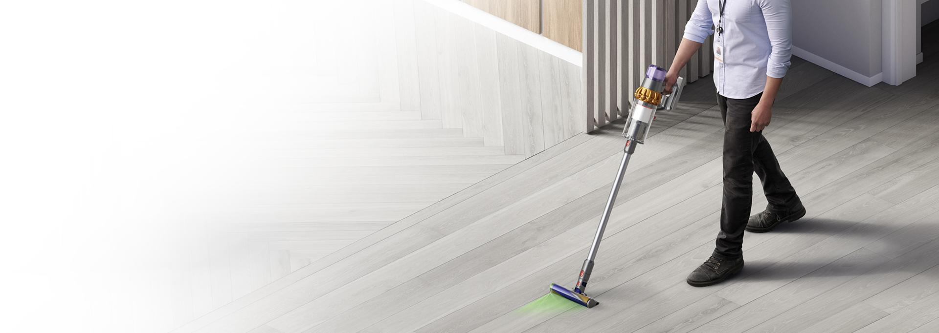 Man cleaning work space with Dyson cordless vacuum