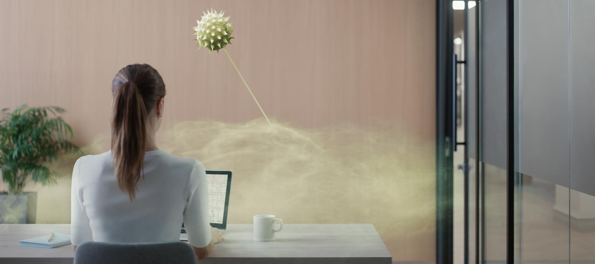 A woman sitting at a desk in an office meeting room. A microscopic image shows pollution in the air.
