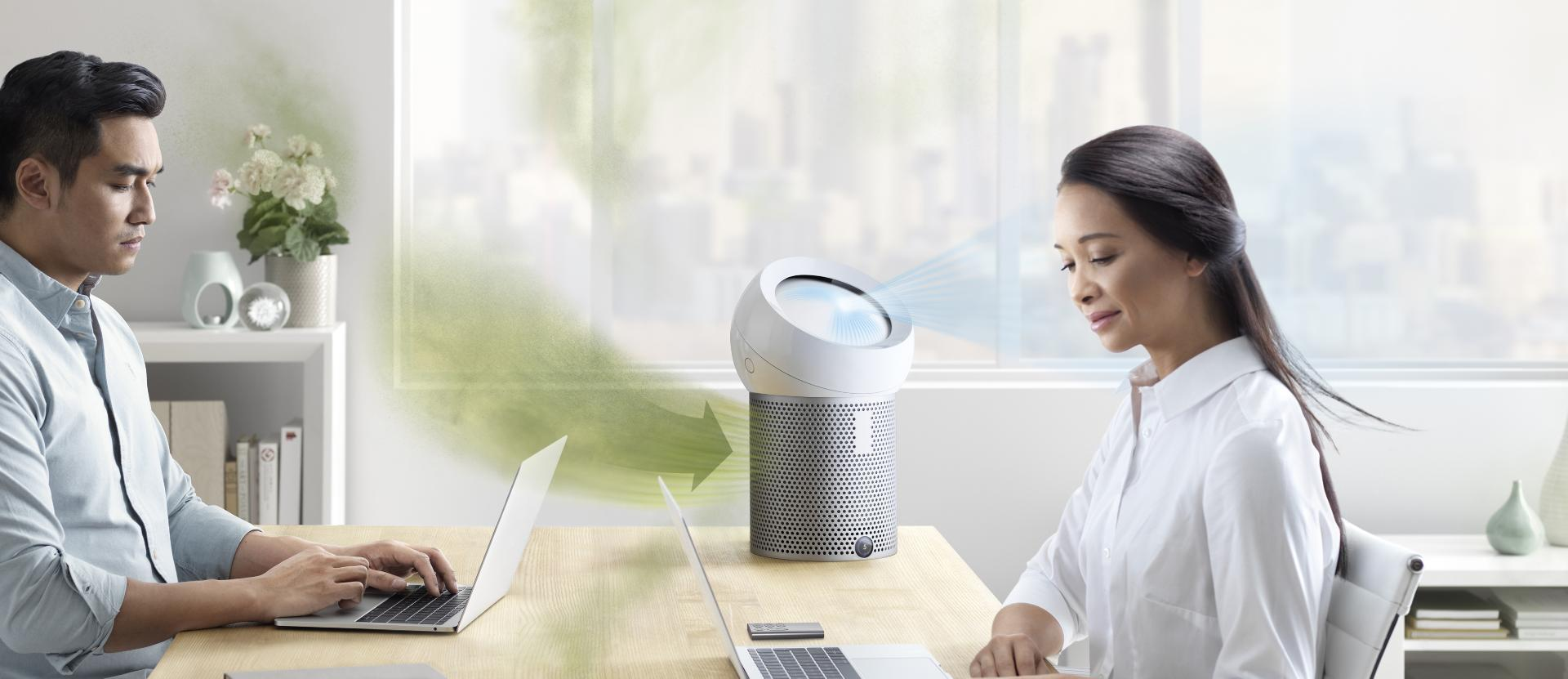 Man and woman sit at desk as Dyson Pure Cool Me ingests polluted air and projects purified air