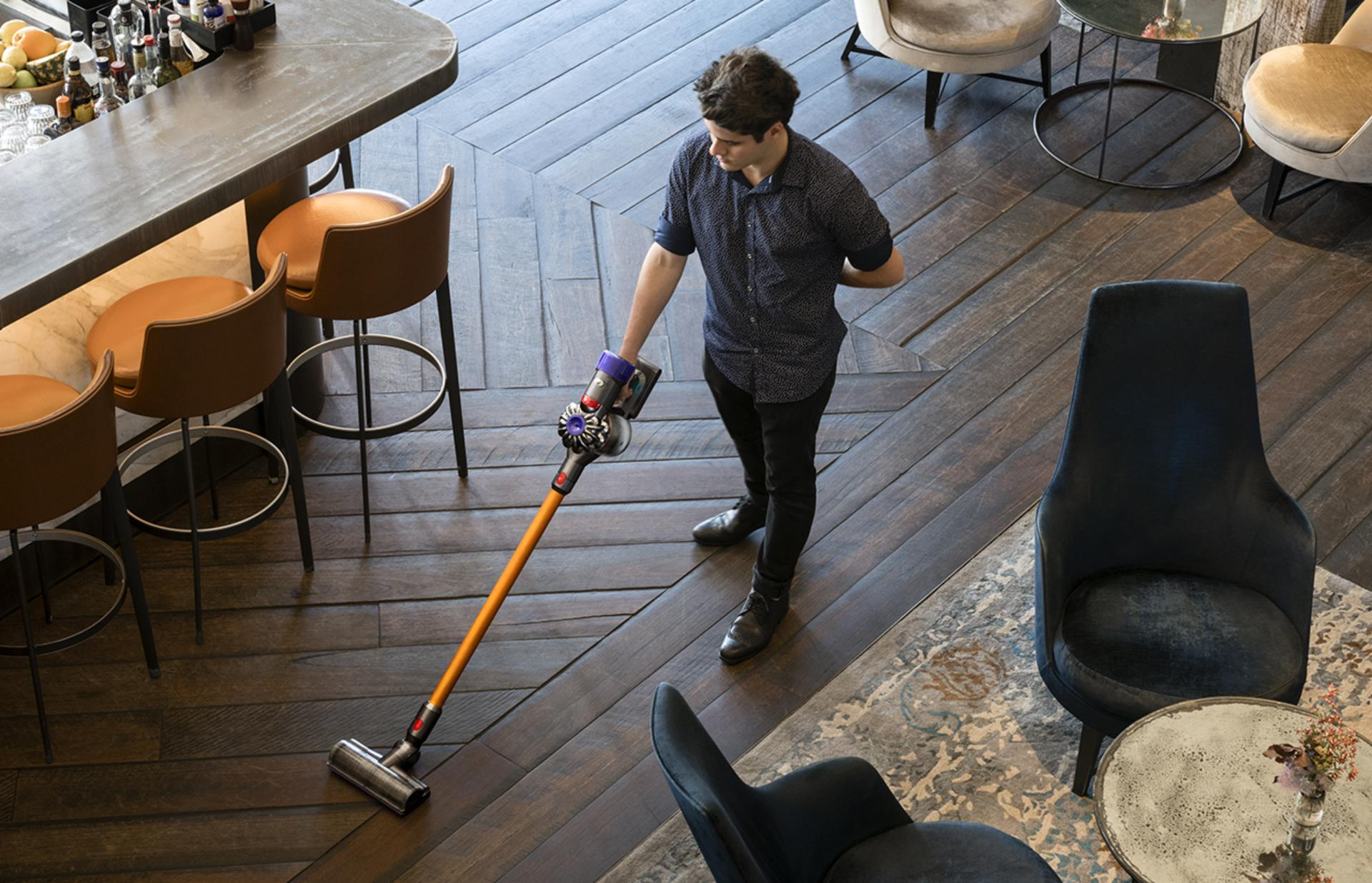 Man using a Dyson vacuum to clean an establishment