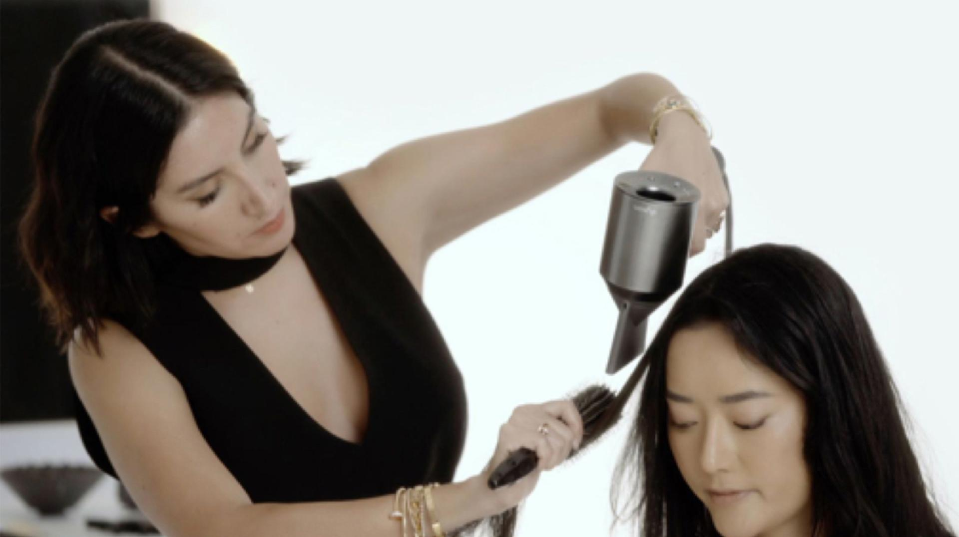 Professional hair stylist using the Dyson Supersonic hair dryer on a customer