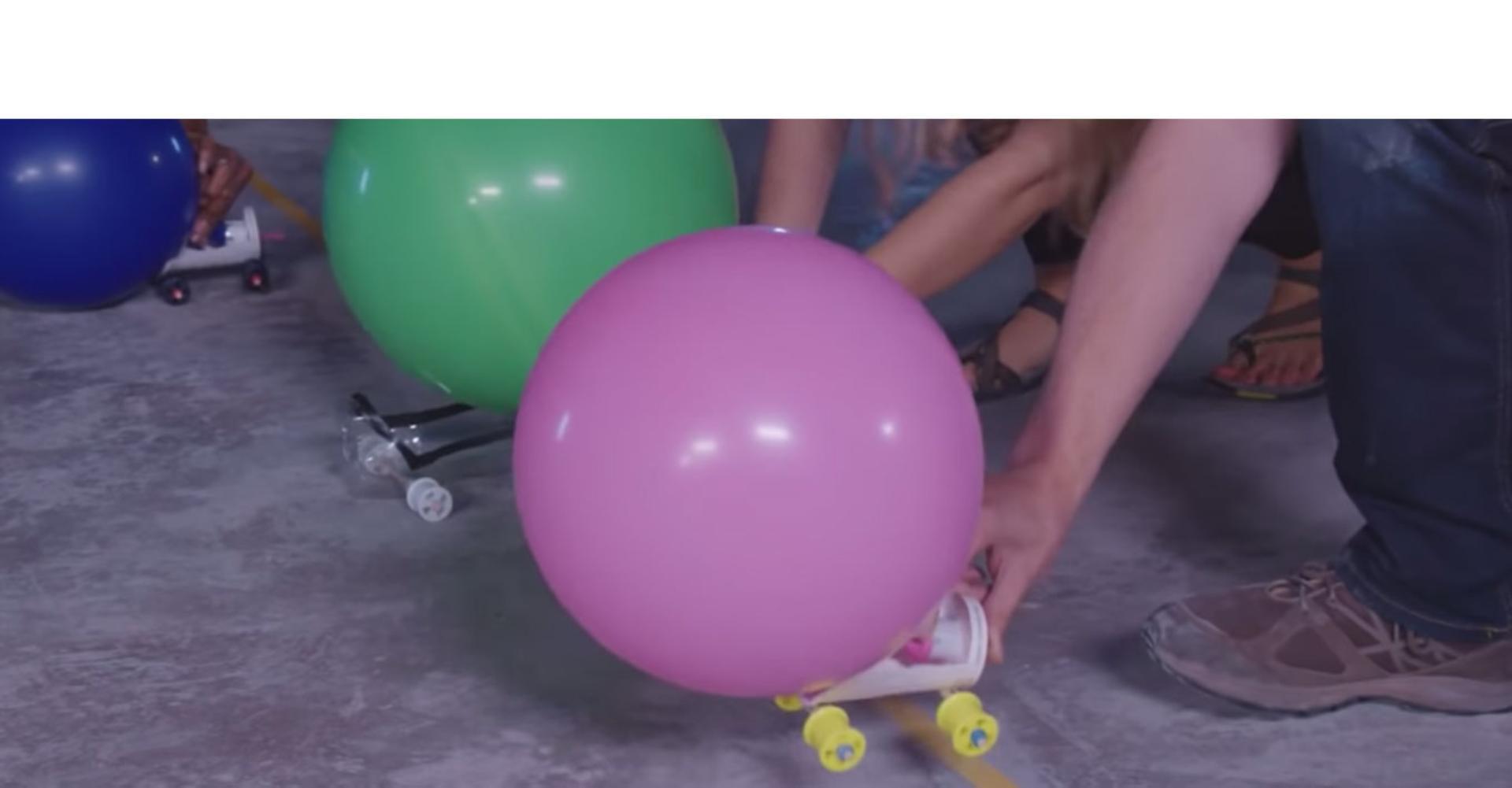 A Dyson engineer shows the balloon powered race car challenge.
