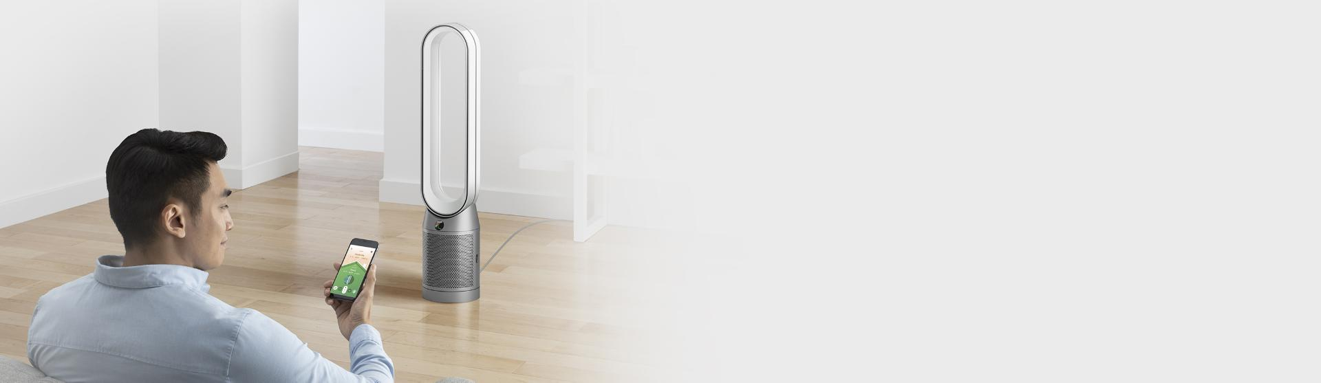 Man sits in front of Dyson purifier using the Dyson Link app on a smart phone