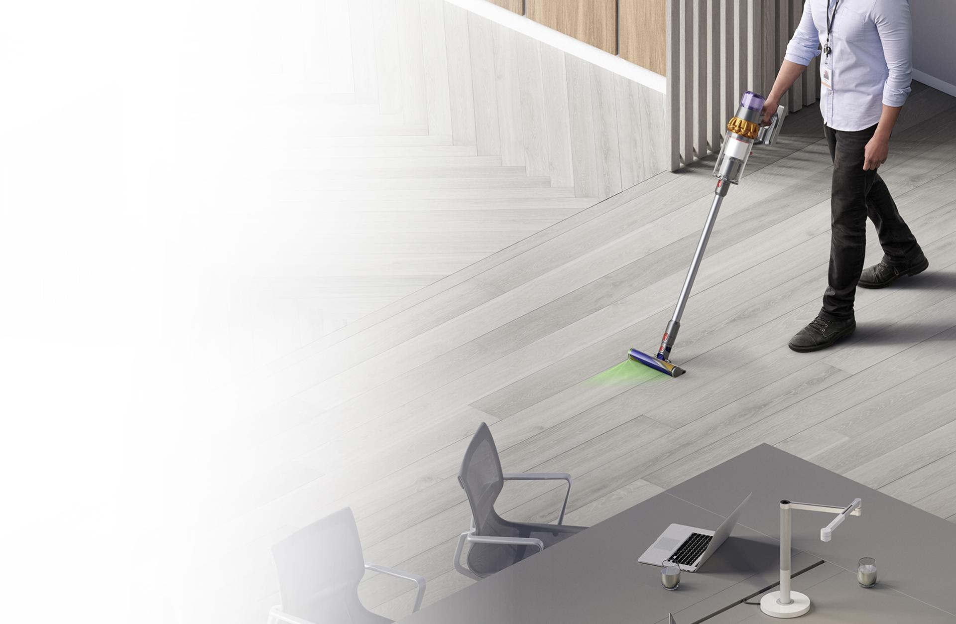 Man cleaning floor with Dyson V15 Detect vacuum