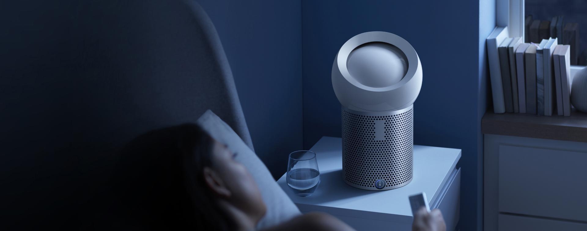 다이슨 퓨어 쿨 미 퍼스널 공기청정기가 옆에 놓여진 침대에 있는 여성