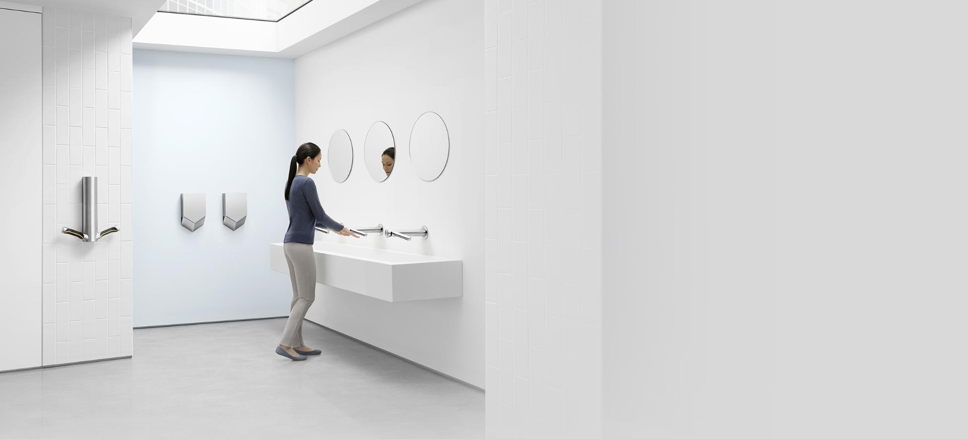 Woman drying hands with the Dyson Airblade Wash+Dry hand dryer