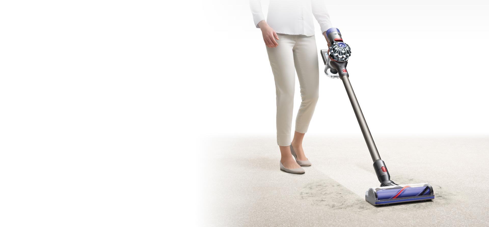 O femeie aspiră covorul cu aspiratorul vertical fără fir Dyson V8