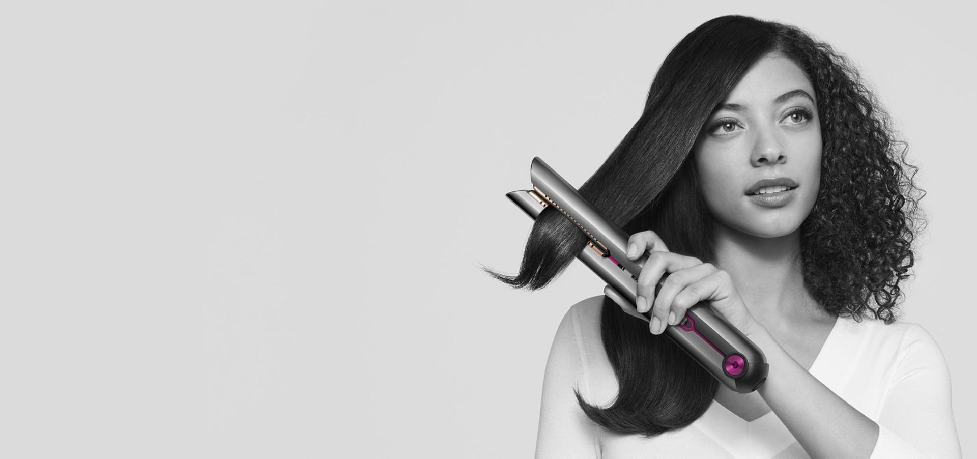 Woman achieving beautifully straight hair with the Dyson Corrale straightener