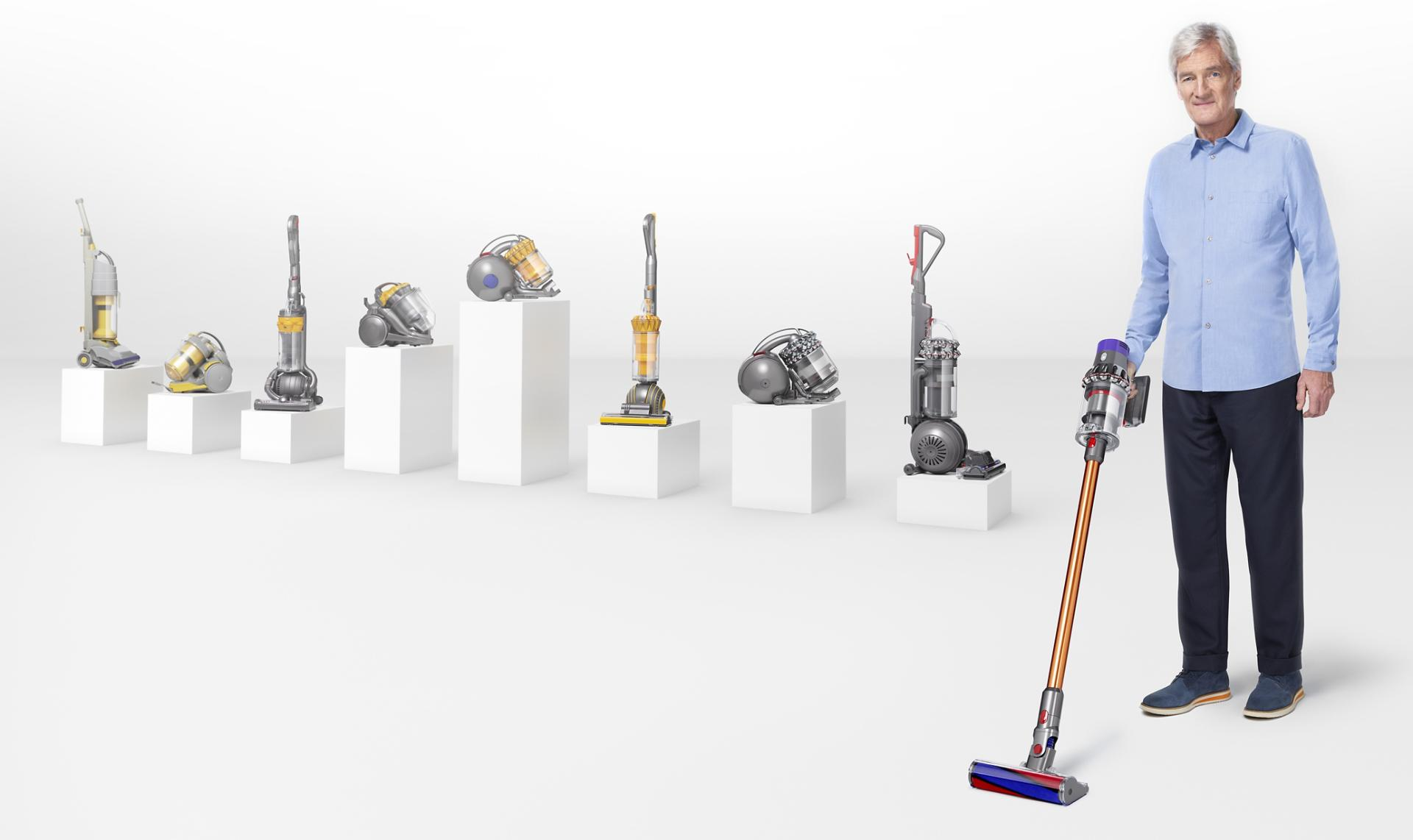 James Dyson with Dyson vacuums from the last 25 years