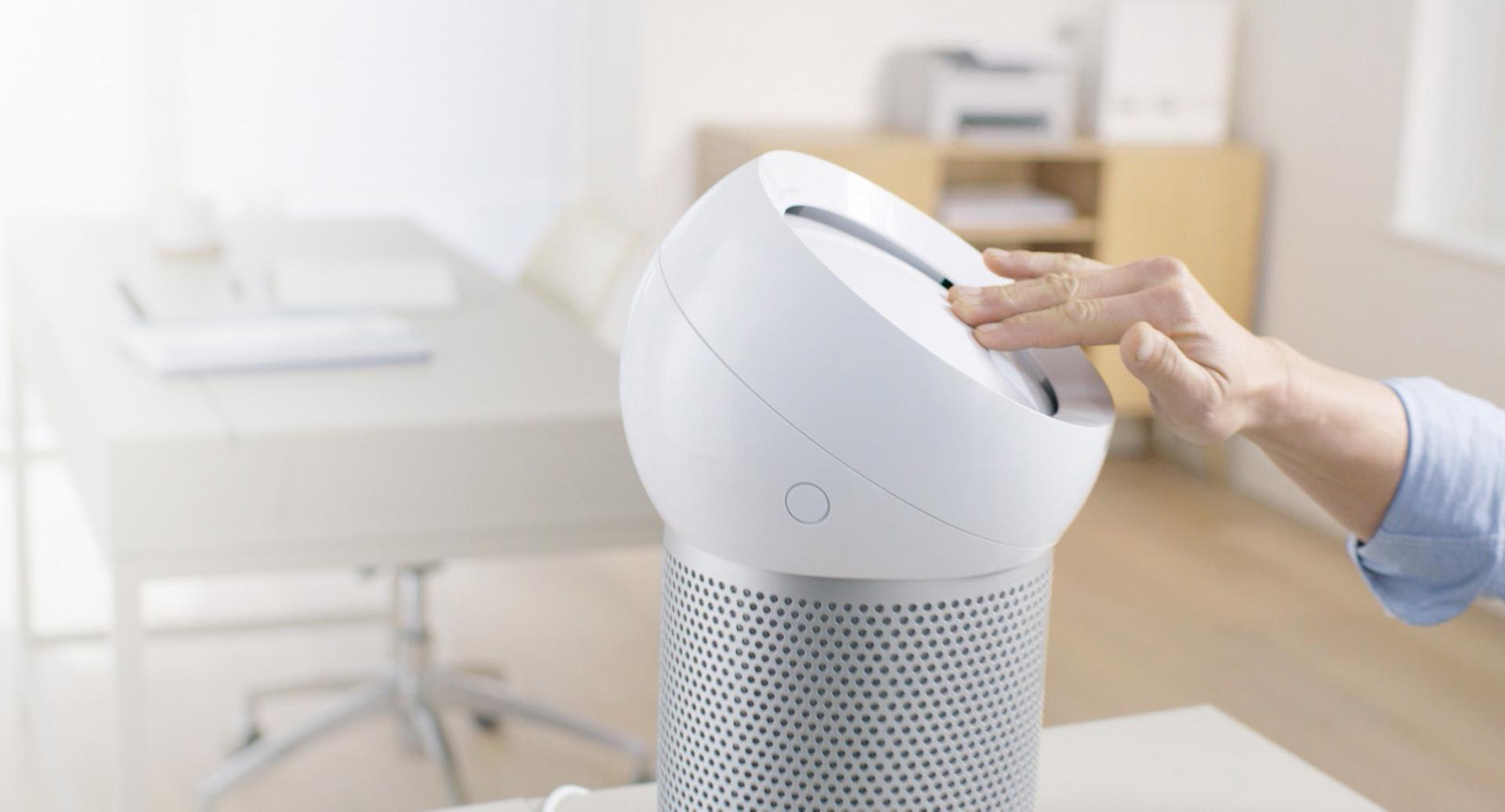 Hand reaches out to refocus airflow on the Dyson Pure Cool Me personal purifying fan