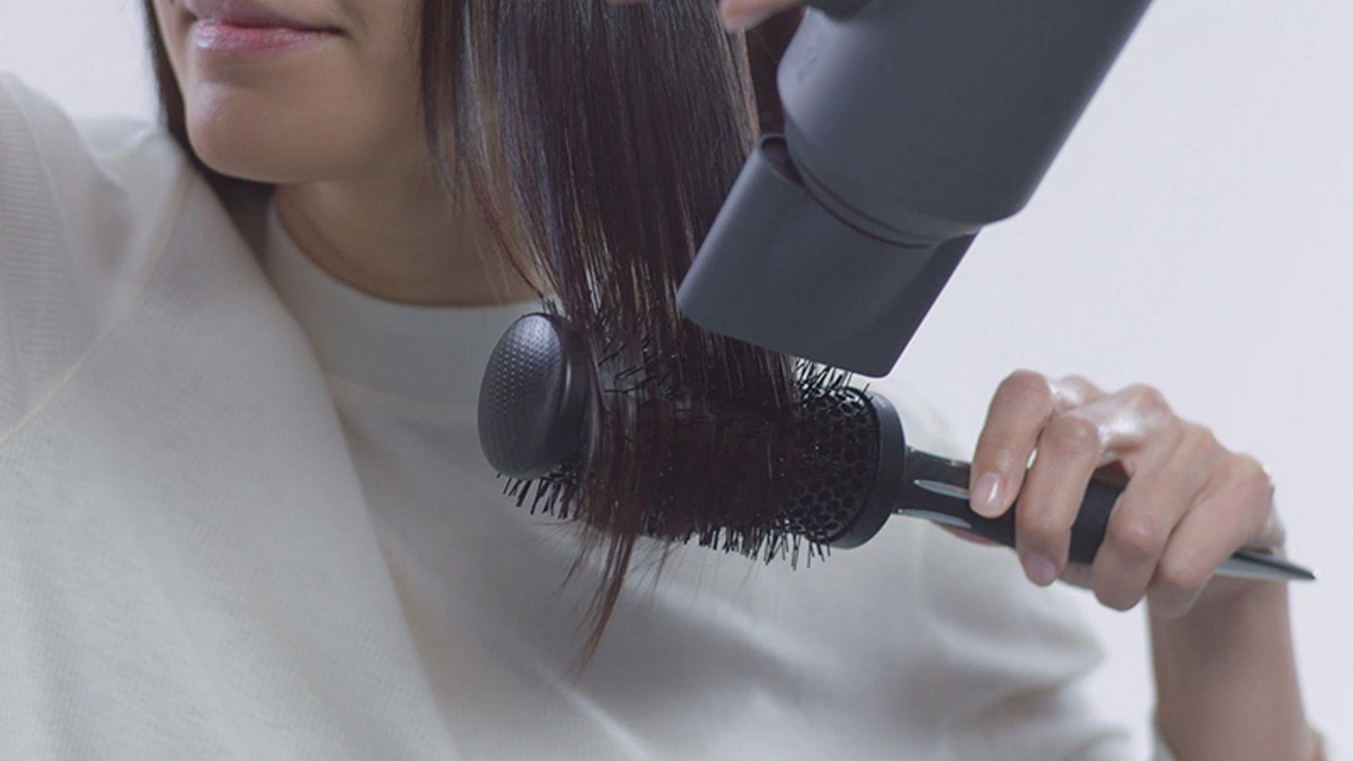 Lady using Dyson Supersonic smoothing nozzle attachment