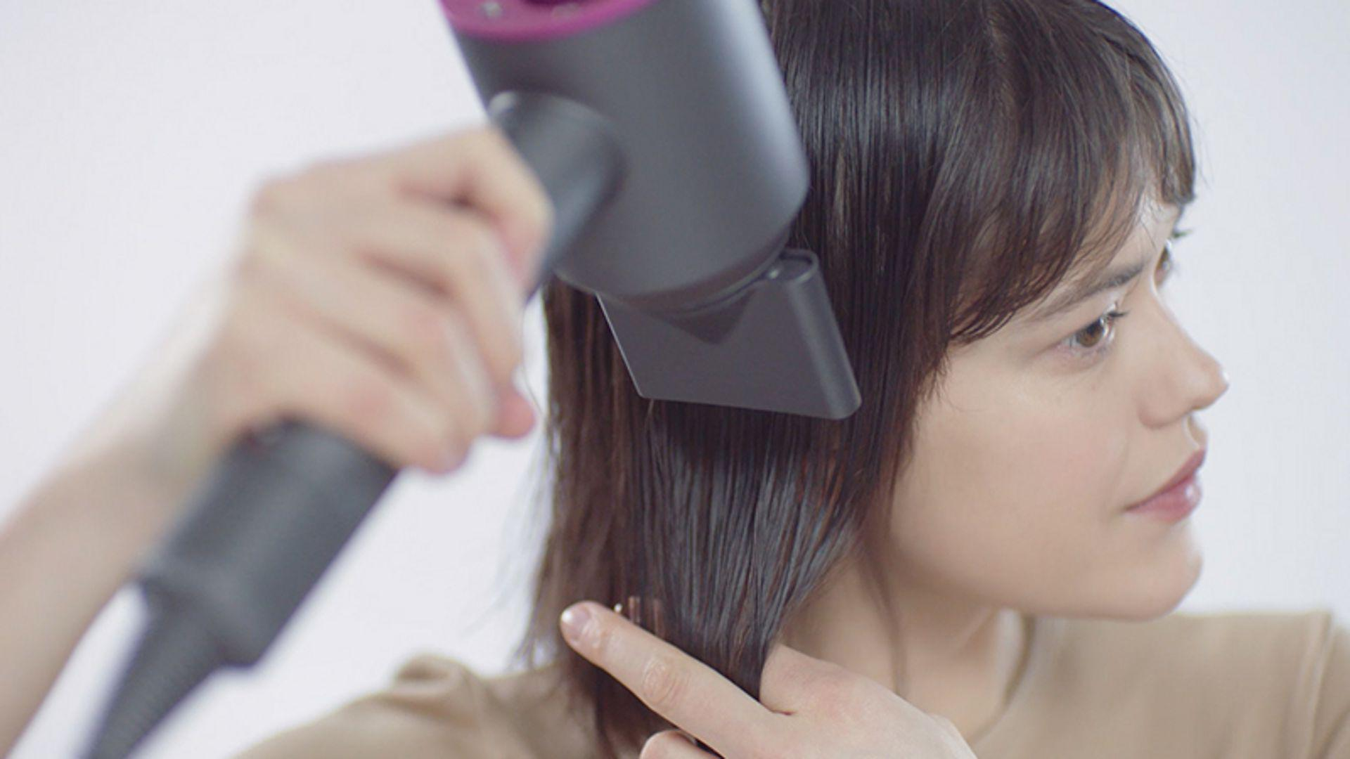 Lady using Dyson Supersonic styling concentrator attachment
