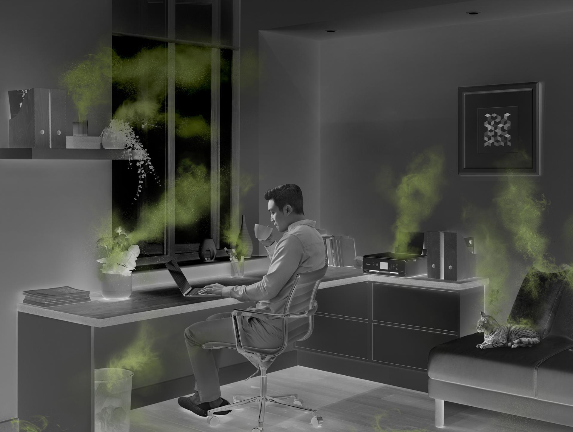 Hombre que trabaja en una oficina en casa, rodeado de fuentes de contaminación del aire interior.