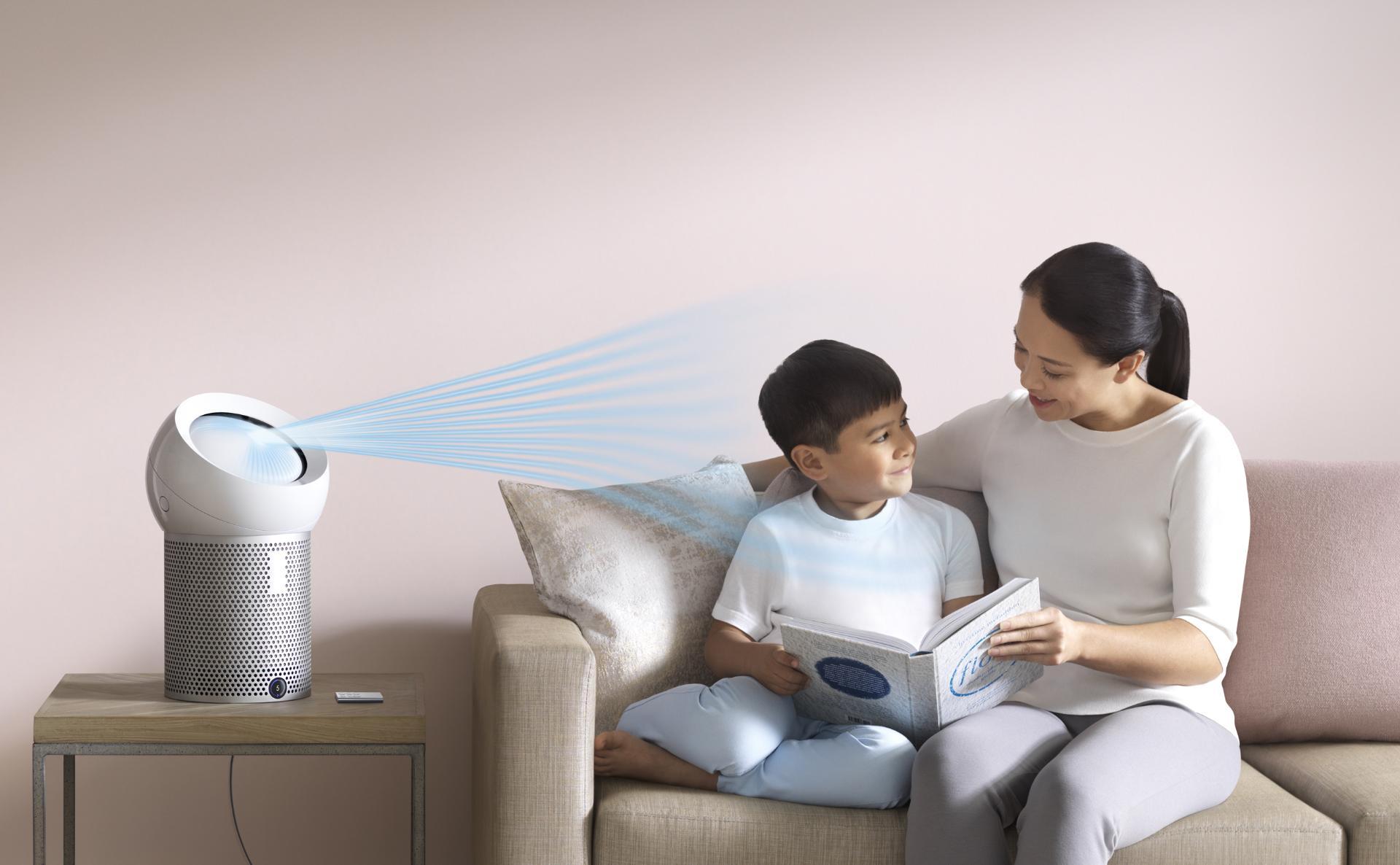 Una mujer leyendo a su hijo, junto a un ventilador Purificador Personal Dyson