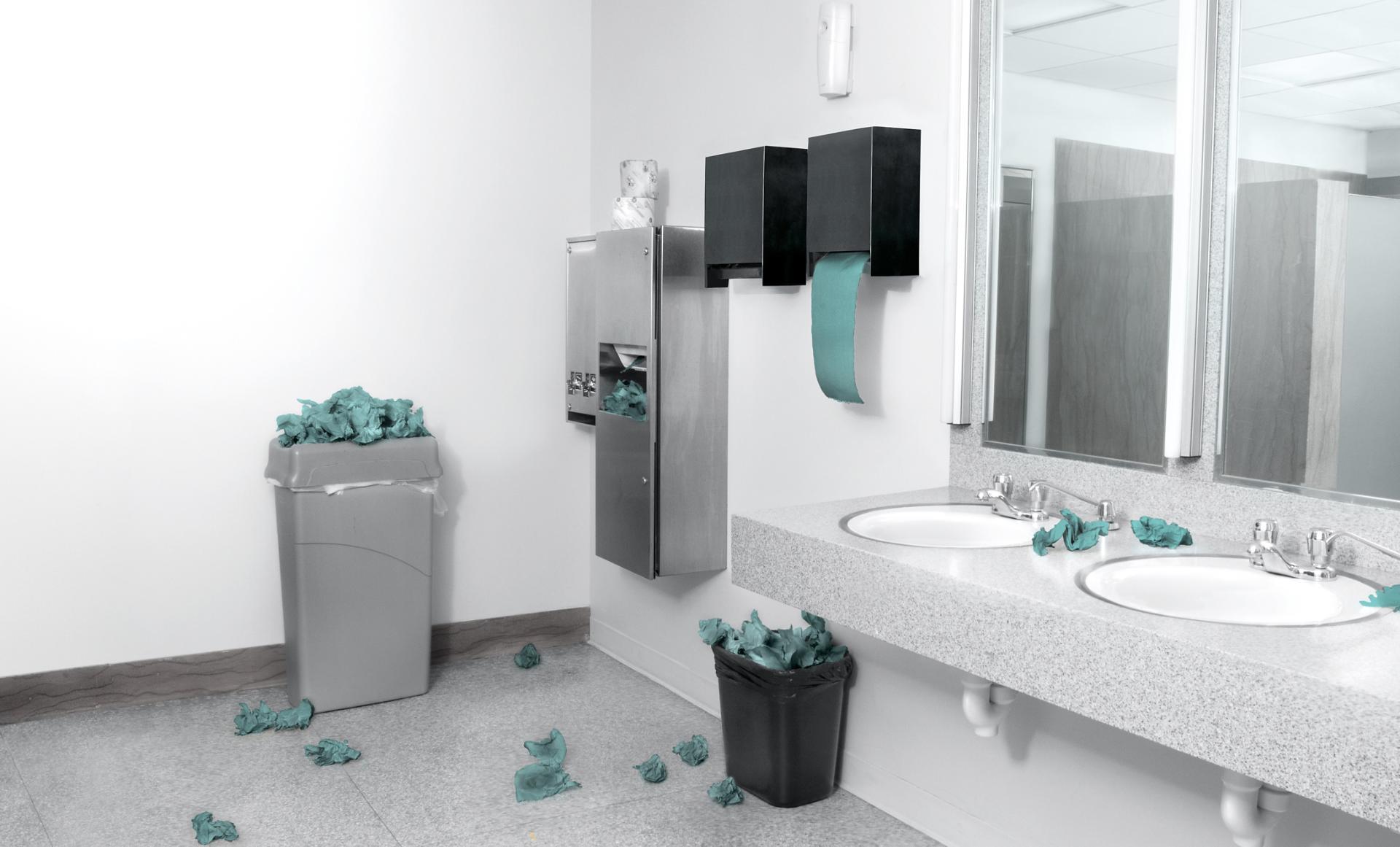 Baño con toallas de papel en el piso y en contenedores desbordados