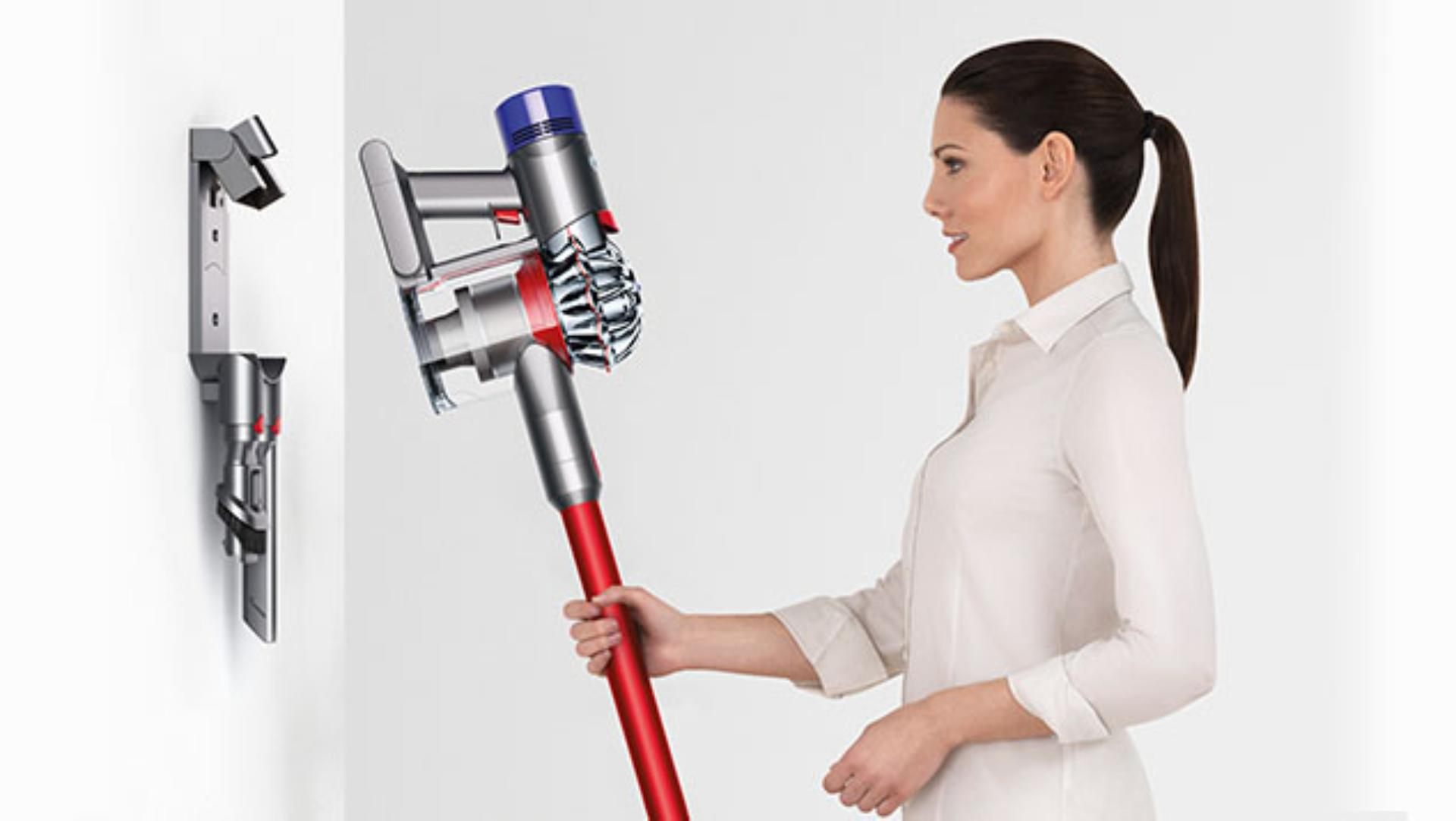 Woman using Dyson V8 Absolute vacuum docking station