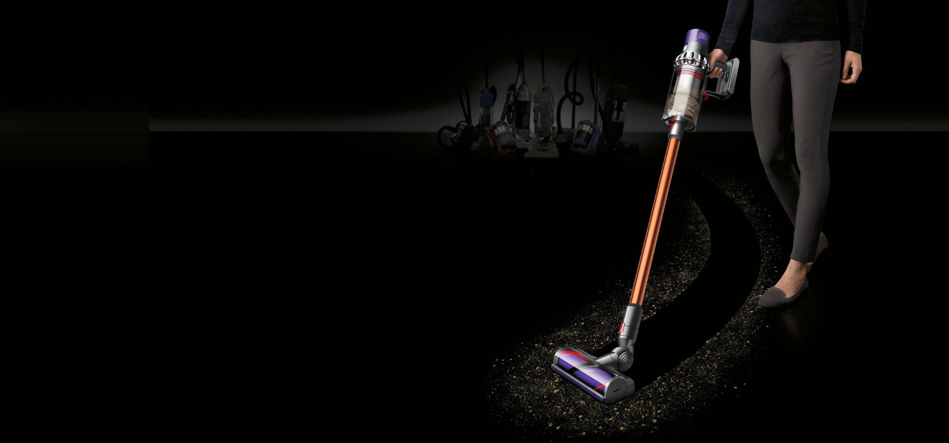 Woman collects dirt using Dyson Cyclone V10 vacuum cleaner.