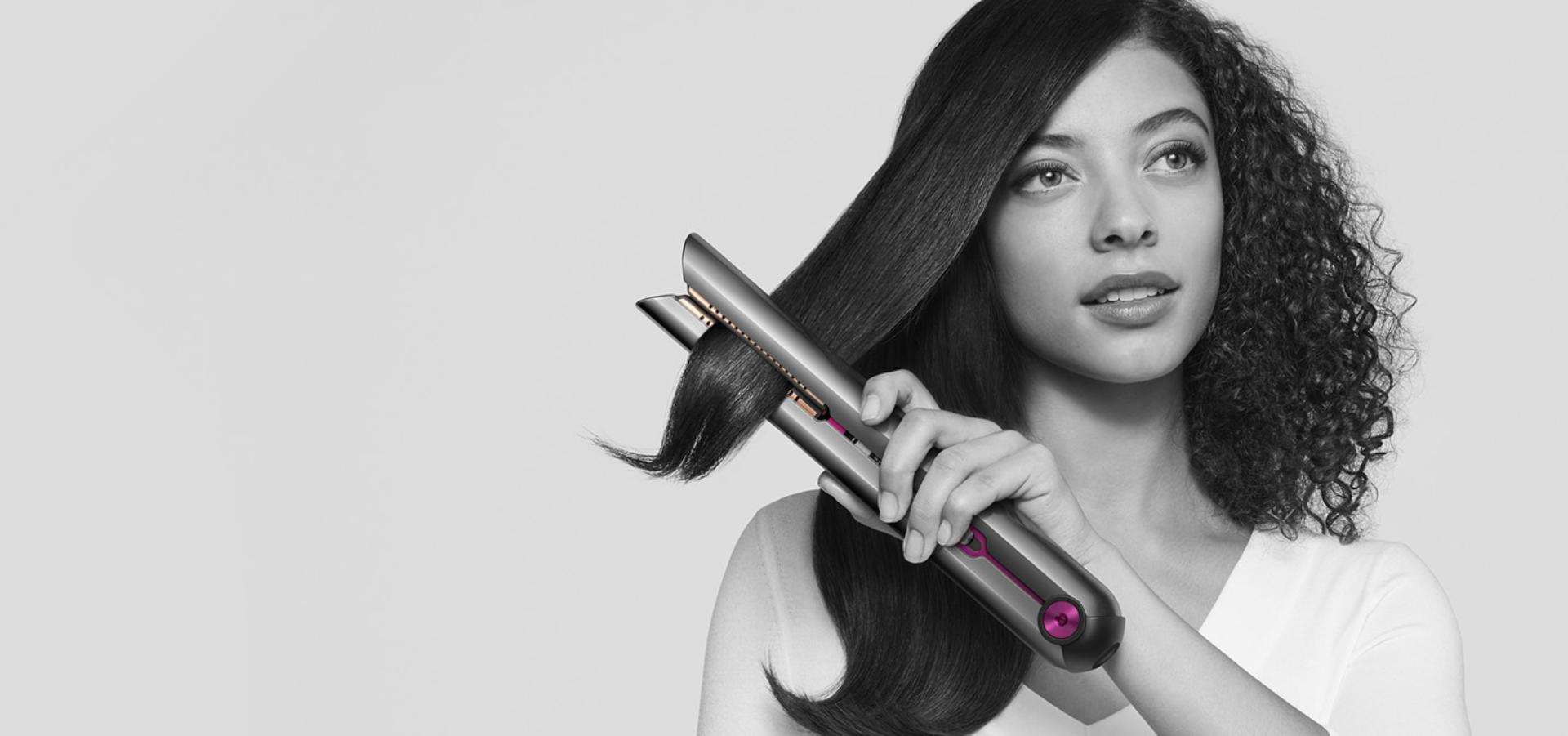 Kadın Dyson Corrale™ saç düzleştiriciyi kullanıyor