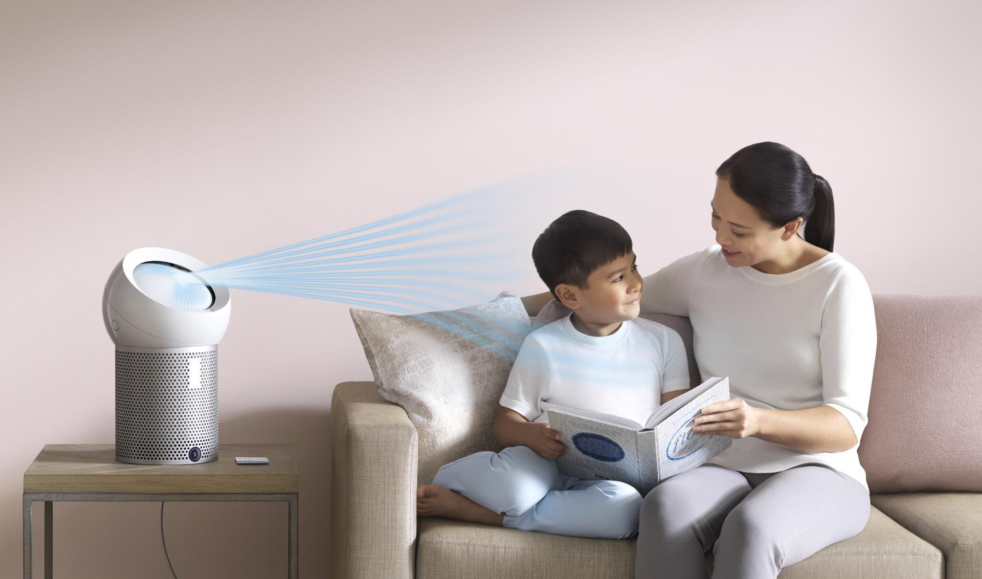 فتى يقرأ كتاباً في فراشه بينما تقوم مروحة دايسون المُنقية الشخصية بضخ تيار هواء بارد تجاهه.