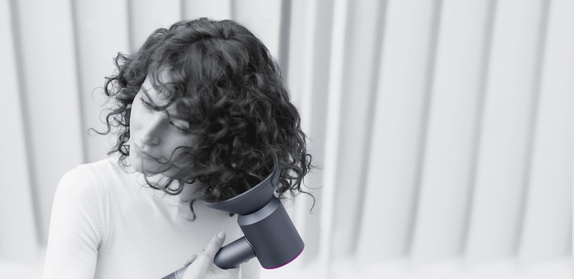 سيدة تُجفّف شعرها باستخدام مجفف الشعر Dyson supersonic