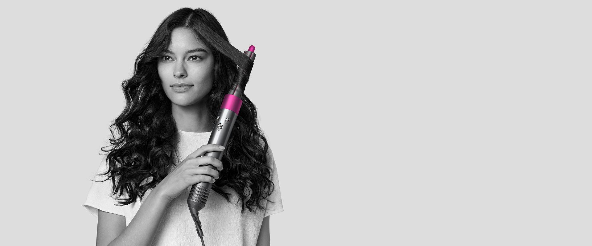Woman curls her hair with Dyson Airwrap styler.