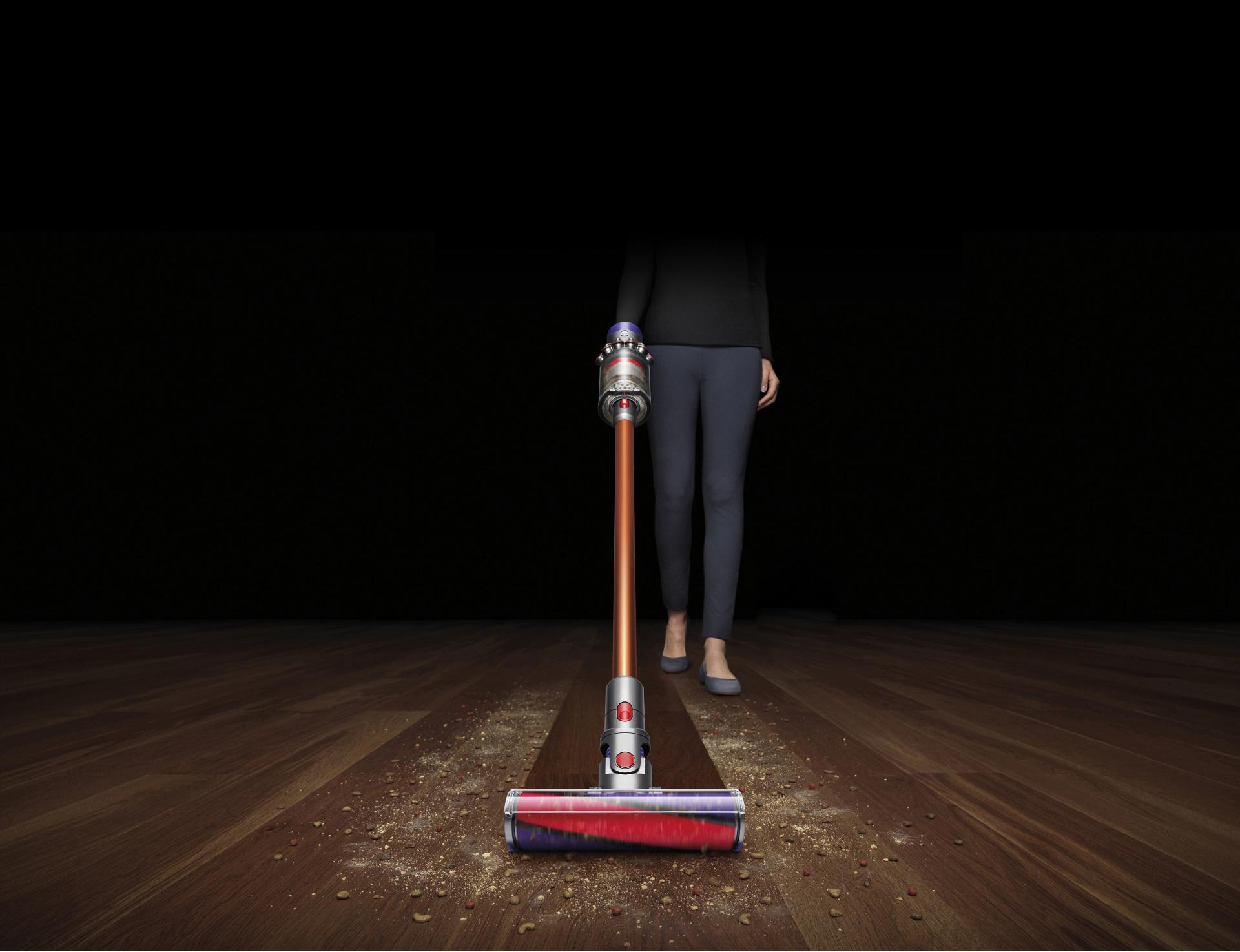 Woman using Dyson Cyclone V10 cord-free vacuum to pick up debris from hard floor