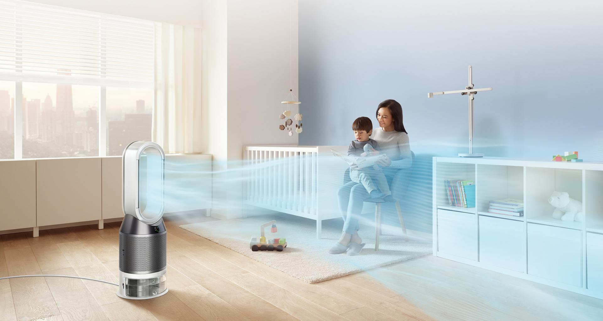 Žena předčítá svému dítěti, zatímco čistička vzduchu s funkcí zvlhčovače Dyson vypouští proud vzduchu do pokojíku