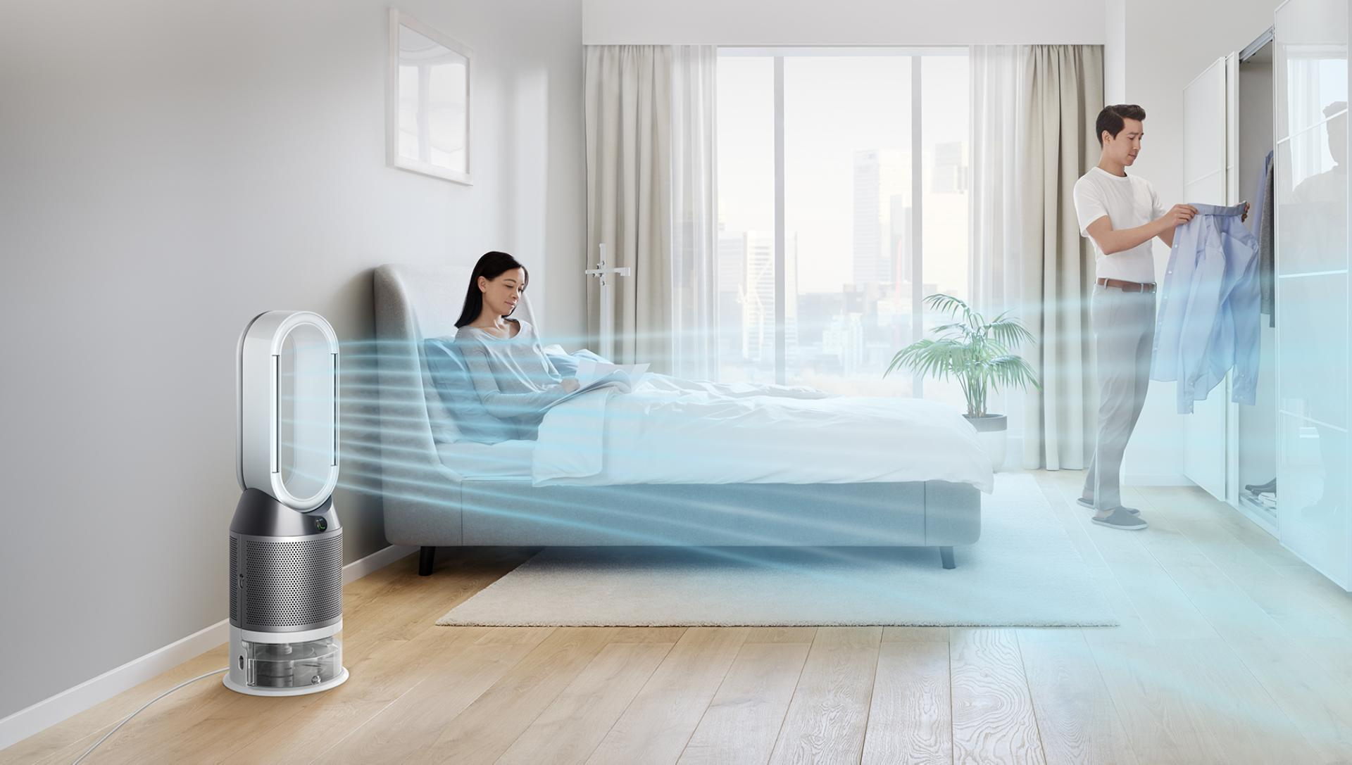A woman relaxes in bed while her Dyson purifier humidifier fan circulates air through the room