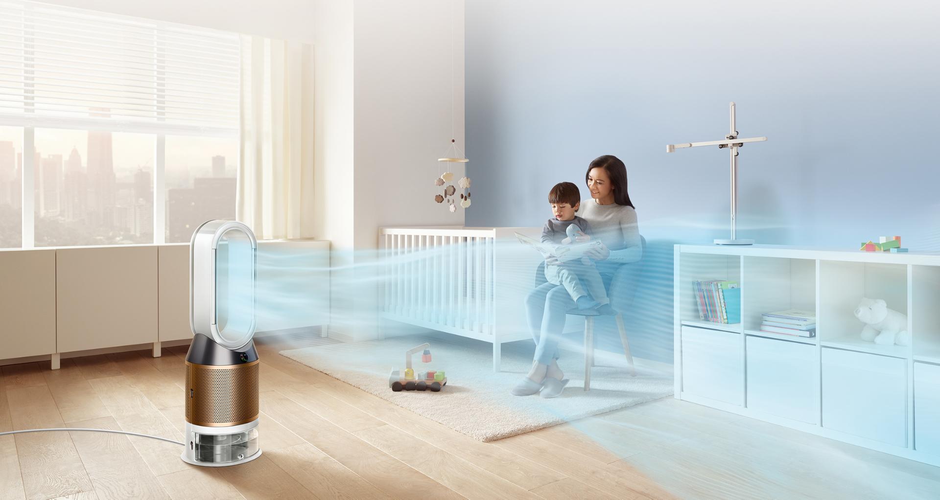 Una mujer lee con su hijo mientras el purificador, humidificador y ventilador Dyson proyecta una corriente de aire por su habitación