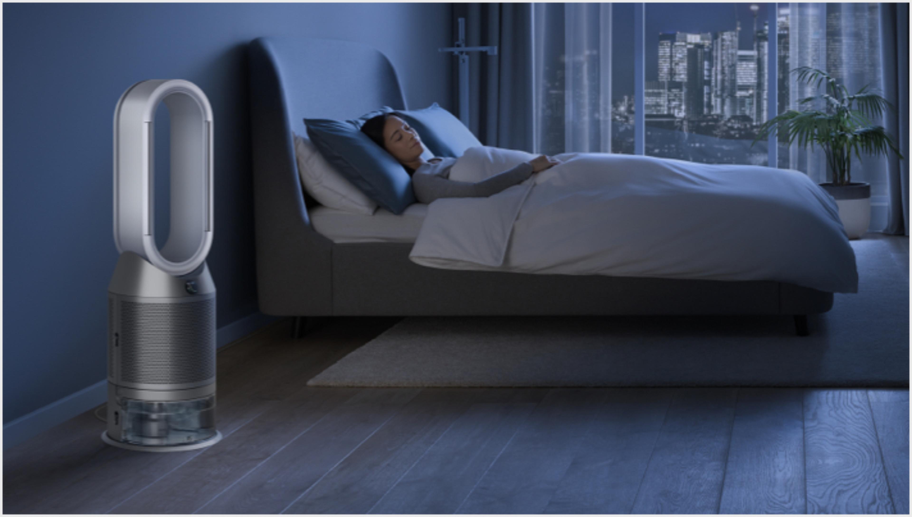 Kobieta w łóżku obok oczyszczacza z funkcją nawilżania Dyson