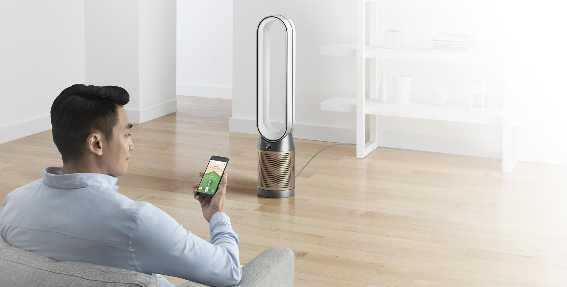 Man controlling Dyson Purifier with Dyson Link app