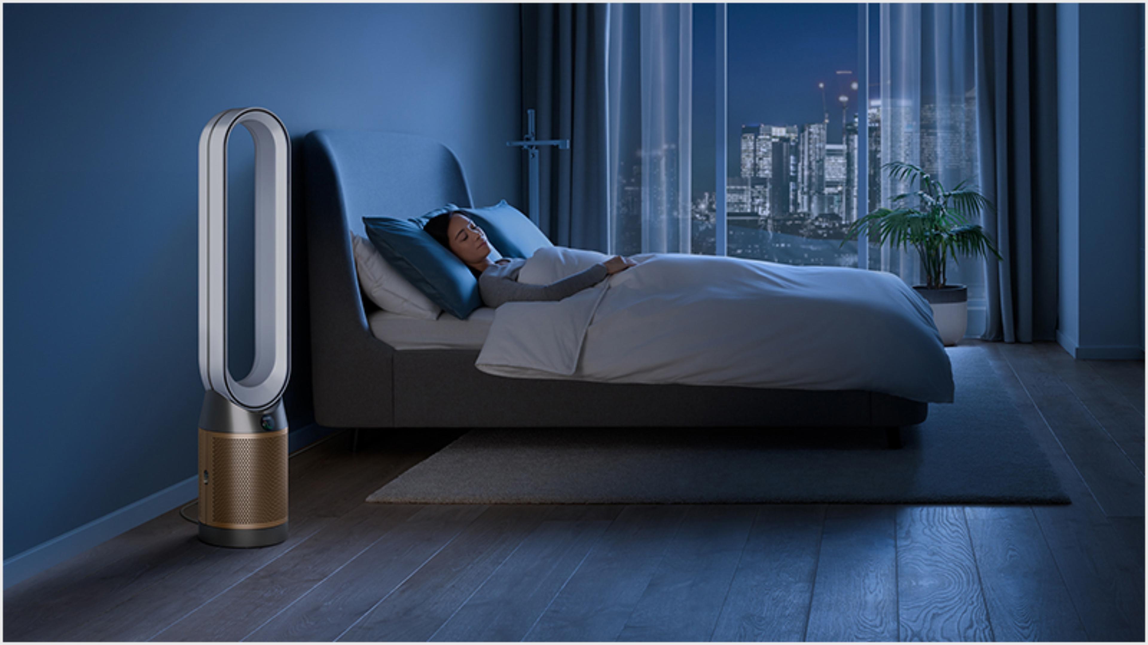 Oczyszczacz Dyson w ciemnej sypialni z osobą spokojnie śpiącą