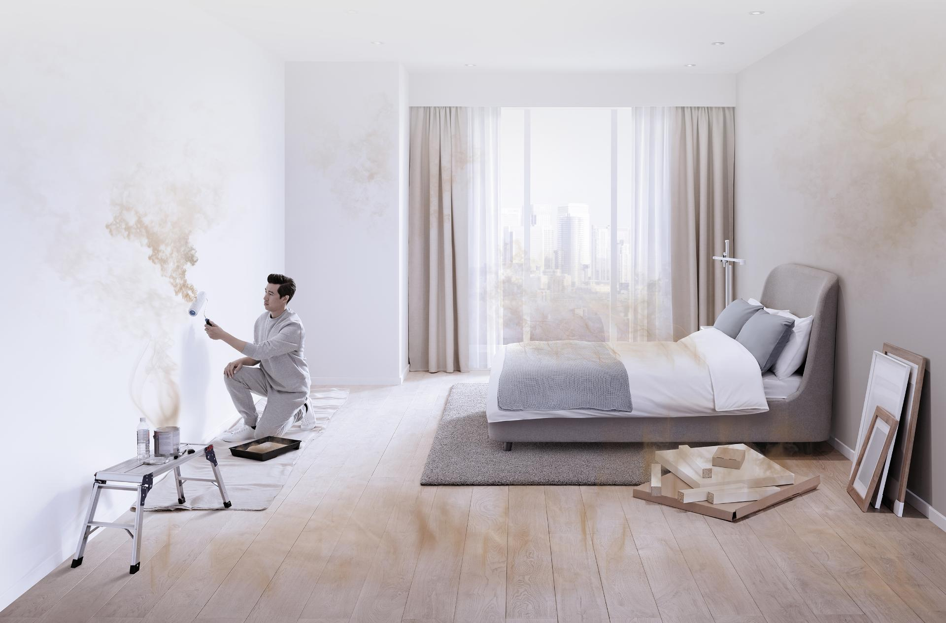 A man paints a room, while particles and gases pollute the air around him