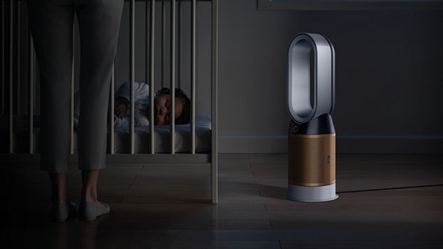 A baby sleeping soundly in their cot, while a Dyson Pure Cryptomic purifier projects purified air in Night mode