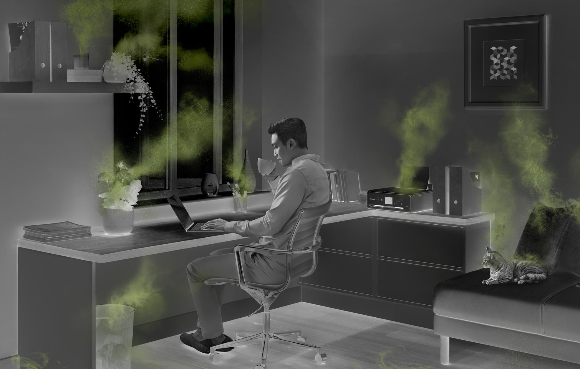 Man working in a home office, surrounded by sources of indoor air pollution