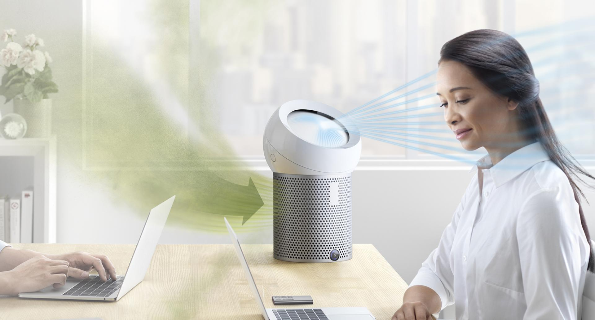An office worker using a Dyson Pure Cool Me personal purifier fan
