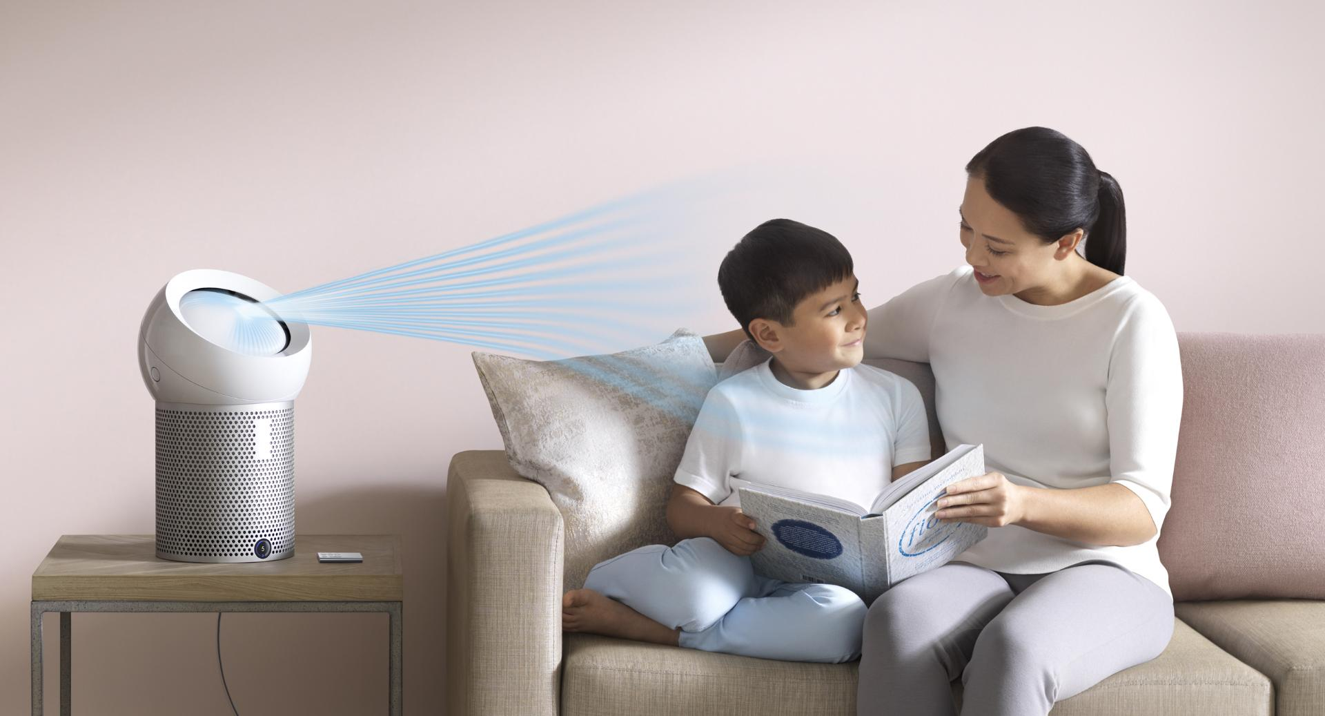 A woman reads to her son, next to the Dyson Pure Cool Me™ personal purifying fan