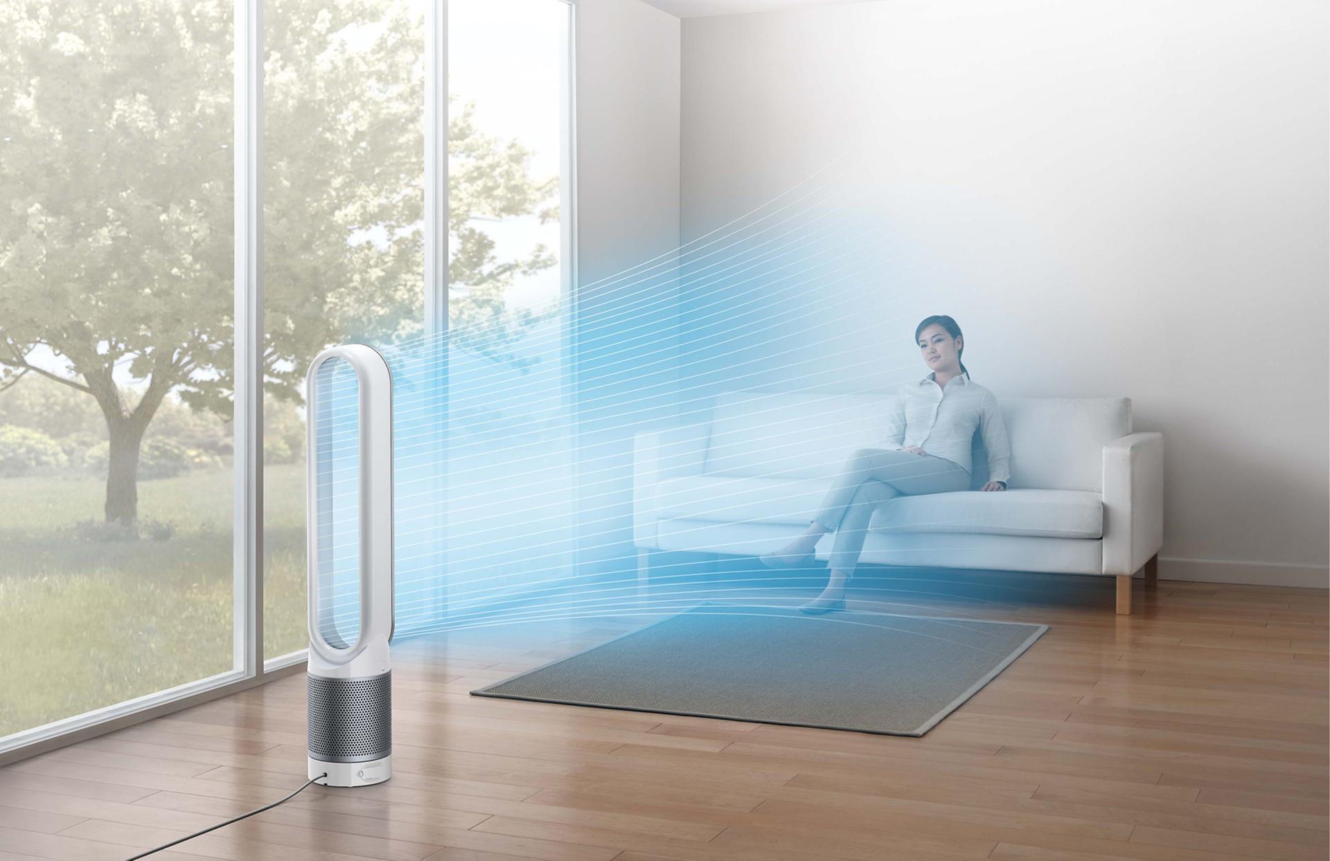Woman sitting on sofa beside Dyson Pure Cool™ purifier fan