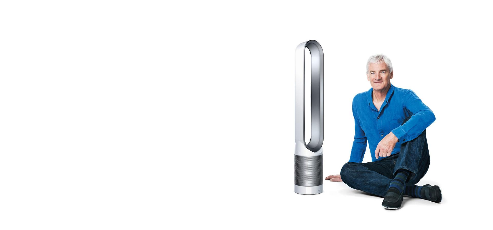 James Dyson sitting beside Dyson Pure Cool™ purifier fan