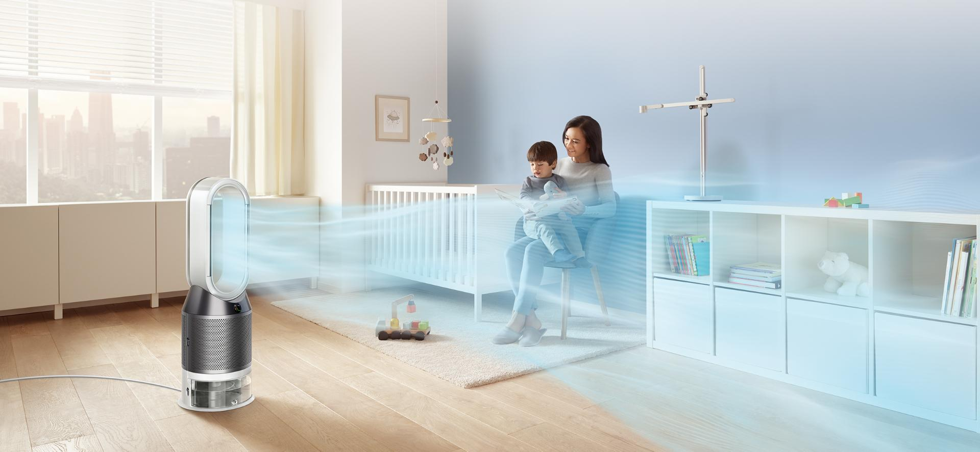 A woman reads to her child while the Dyson purifier humidifier fan projects a stream of air through his bedroom