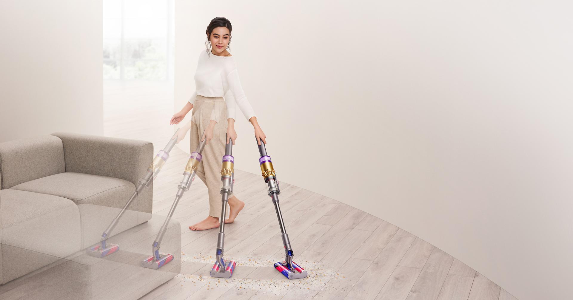 אישה שואבת רצפה סביב ספה עם שואב Dyson Omni-glide™