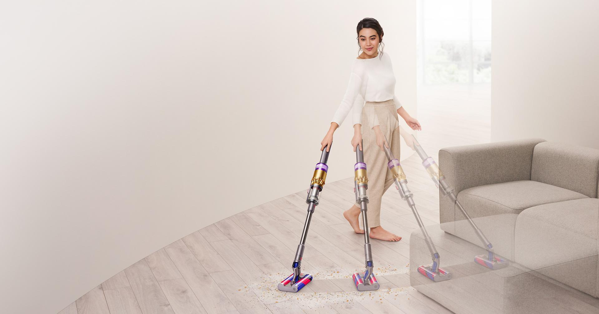 다이슨 옴니-글라이드™ 무선 청소기로 소파 주변의 마룻바닥을 청소하는 여성.