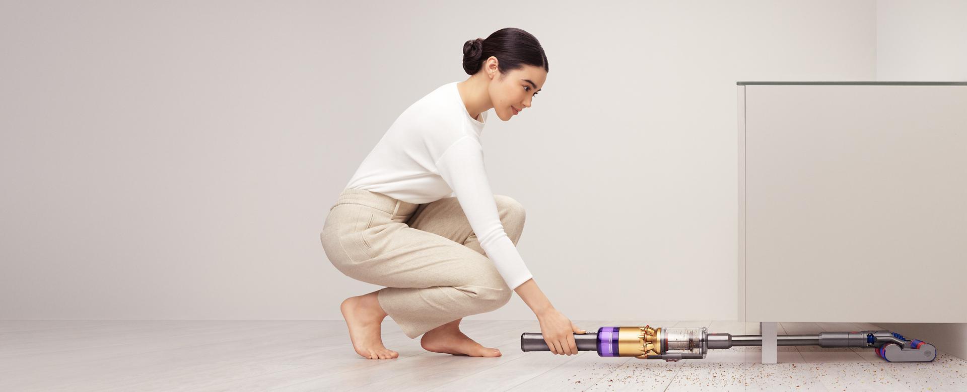 다이슨 옴니-글라이드™ 무선 청소기로 장식장 아래를 청소하는 여성.