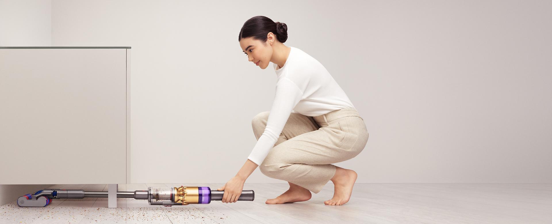 سيدة تَستخدم مكنسة Dyson Omni-glide™ للتنظيف أسفل خزانة.