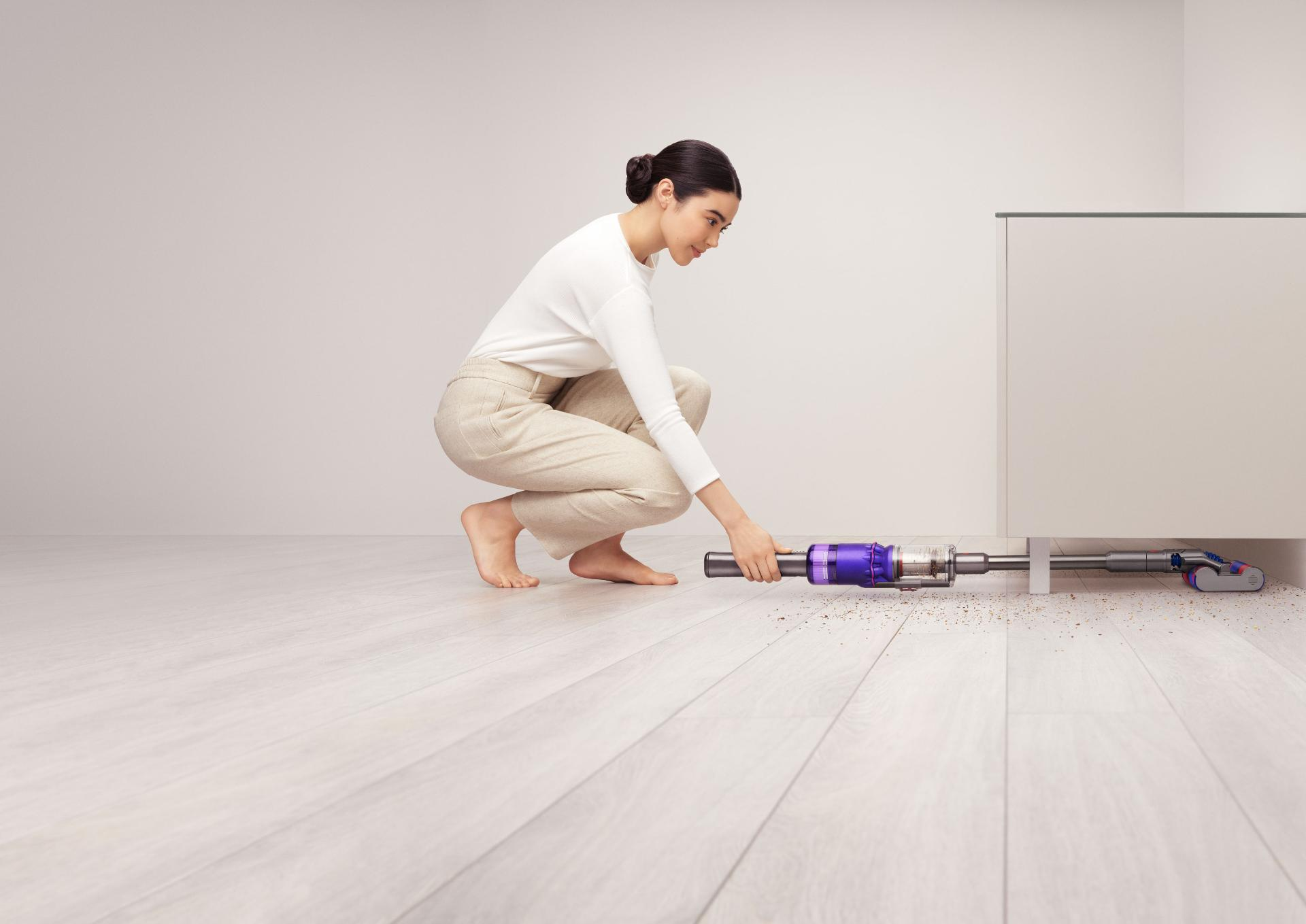 Woman using Dyson Omni-glide™ vacuum to clean under a cupboard.