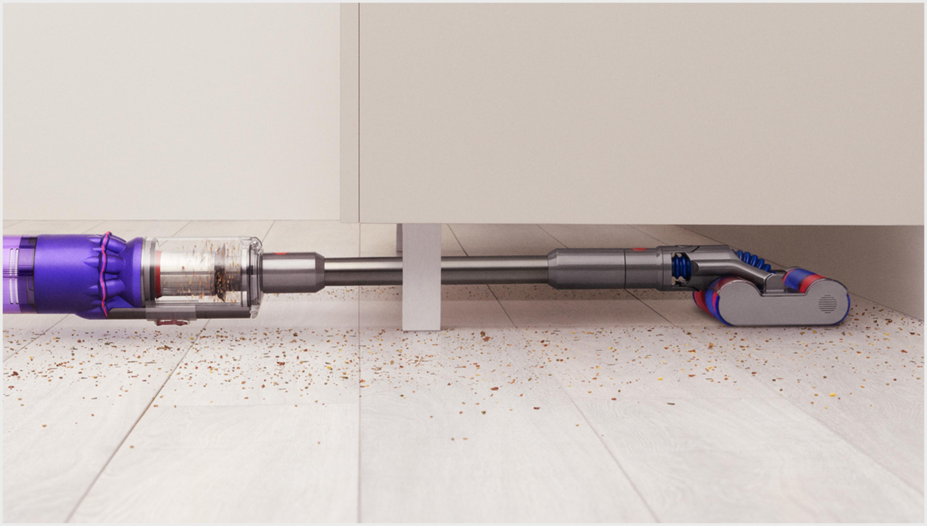 다이슨 옴니-글라이드™+ 무선 청소기로 낮은 가구 아래를 청소하는 모습.