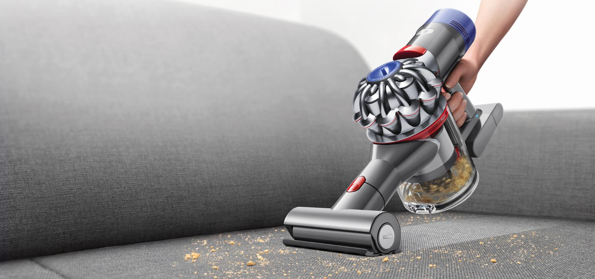 The Dyson V7 Trigger handheld vacuum cleaner being used to clean sofa