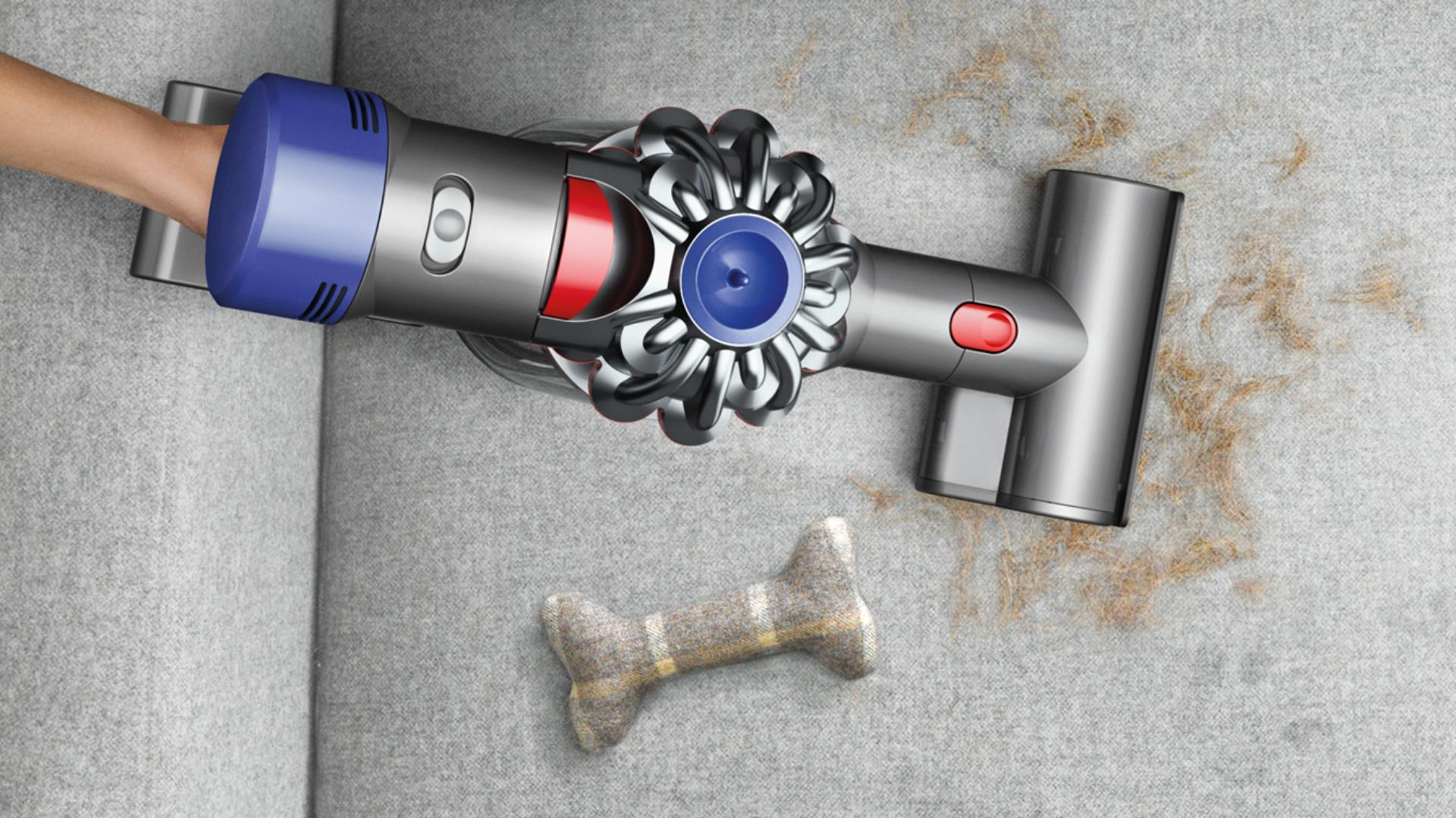 Dyson V7 handheld vacuum cleaner cleaning sofa after pet