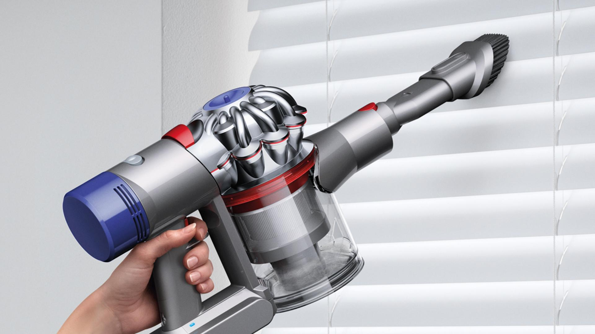 Dyson V7 handheld vacuum cleaner being used to clean awkward area